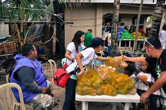 Laying out bags on the table in preparation of distribution. (Photo Credit: Elero Soberano of Discover Panay Island)